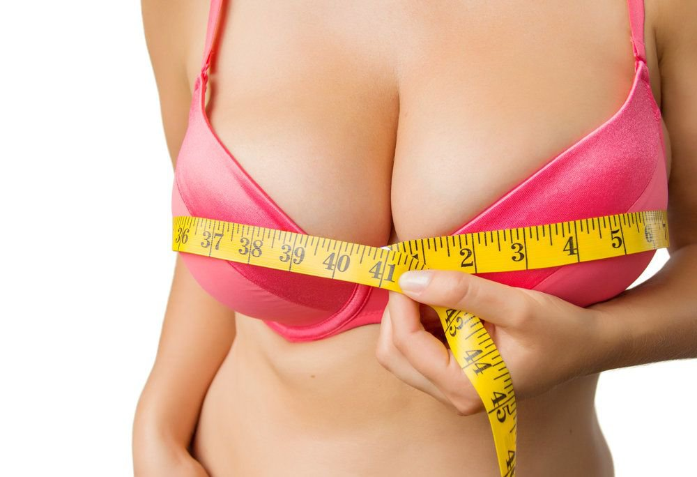 A woman in a pink bra measuring her breasts